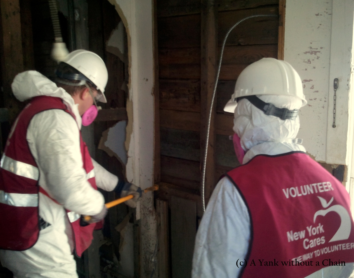 New York Cares volunteers working on tearing down a wall