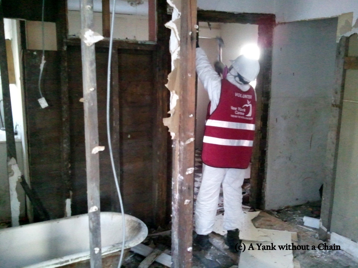 A New York Cares volunteer pulling down moldy walls