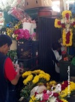 You can see men and women arranging flowers on the second floor of San Camilo Market