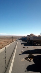Trucks wait on the road to Uyuni for the protest to be disassembled