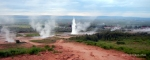 Strokkur erupting, with a view of smaller geysirs surrounding it