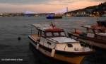 Some boats with the lit up Bosphorus Bridge in the background