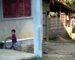 A child playing with a tire in Ban Houay Thong