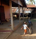A young boy playing with a tire at Ban Houay Thong Village
