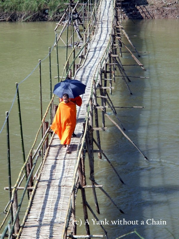Monks walking across a bamboo bridge in Luang Prabang