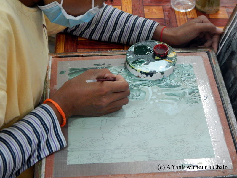 A woman painting a piece at the Artisans Angkor workshop