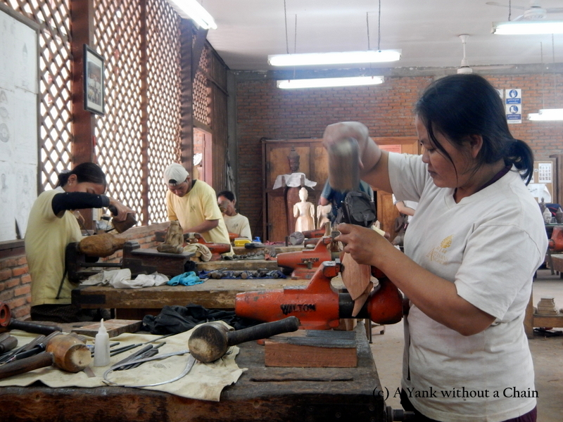 A woman carving a piece at the Artisans Angkor workshop