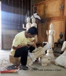 A man carving a piece at the Artisans Angkor workshop