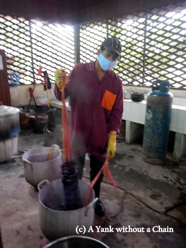 A man demonstrating how the silk is dyed