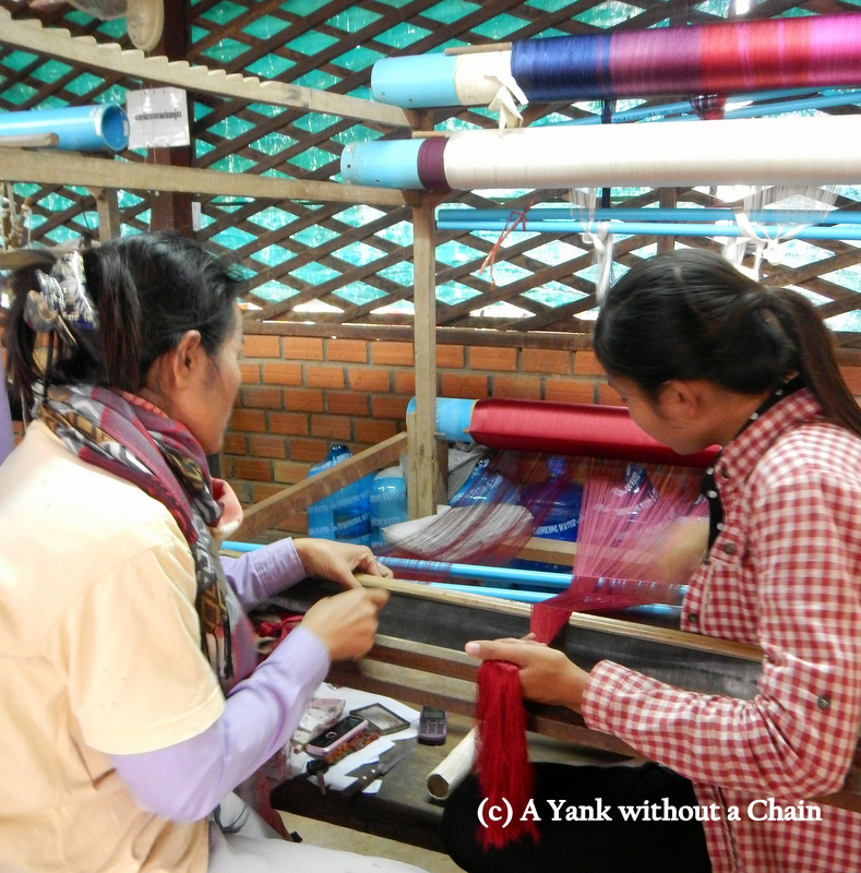 Women demonstrating how a weaving frame is set up at the silk farm