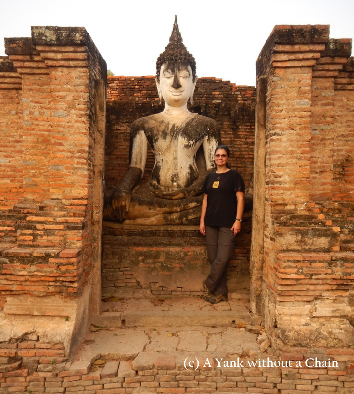 Standing in front of a Buddha statue at Wat Mahathat at Sukothai Historical Park